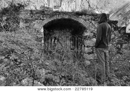 Hooded Man Next To Arched Recess Of Rural Ruin