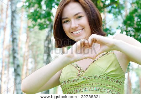 Girl at the park showing a heart sign