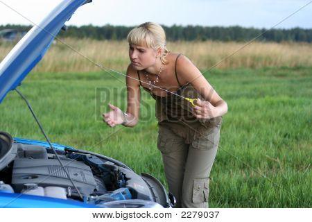 Junge blonde Frau mit ihrem defekten Auto. Das Mädchen ist traurig
