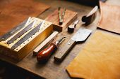 Leather craft or leather working tools on craftmans work desk or workbench. poster