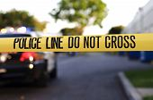 picture of police  - yellow police crime scene tape with a blurred police car in the background.