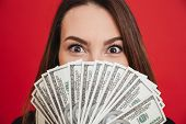 Close up portrait of a pretty girl holding bunch of money banknotes at her face isolated over pink b poster