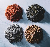Four piles of goji berries, pumpkin seeds, sunflower seeds, Brasilian nuts and almonds. Healthy snac poster
