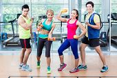 Sportsmen and sportswomen executing functional training routine with dumb-bells in gym poster