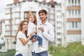 Cute Little Girl Smiling Showing Thumbs Up Her Parents Holding Keys To Their New Home In Apartment B poster