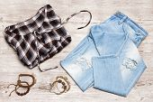 Hippie Fashion Style Women Outfit. Cotton Check Shirt, Ripped Jeans, Rope Wood Bead Bracelets On Sha poster