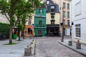 View of small cobblestone street with little bar, shops and typical architecture in Paris, France. poster