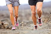 Runners running shoes on trail run. Ultra running athletes legs closeup on desert trail. poster
