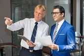 Senior Businessman Pointing Finger And Showing Something To Junior Partner At Office Cafe. Business  poster