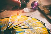 Tarot cards dowsing tool in hand and crystals as a concept of psychic advisor or ways of divination poster
