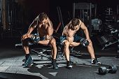 Two Men Bodybuilders Execute Exercise With Dumbbells For Biceps Sitting In Dark Gym Looking On A Bic poster