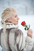Attractive blond woman with a red rose