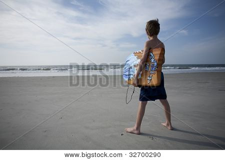 Young Boy at the Beach with a Boogie Boards