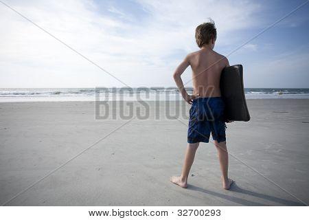 Menino na praia com um Boogie Boards