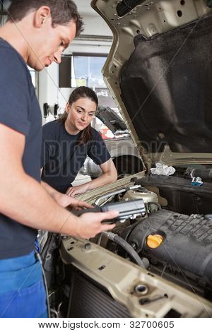 Two mechanic workers with diagnostics tool
