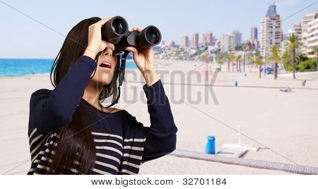 portrait of young woman looking through a binoculars against a beach