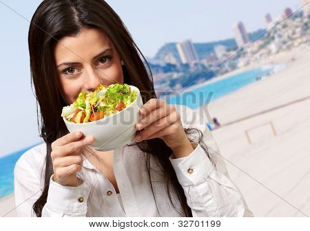 portrait of young woman holding a fresh salad against a beach