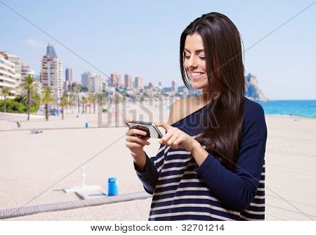 portrait of young woman touching a modern mobile against the beach