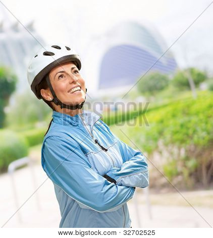 portrait of a sporty middle aged woman wearing a bicycle helmet