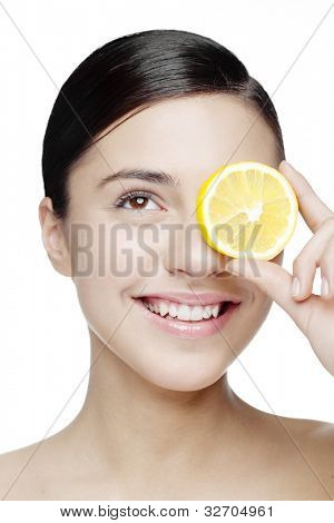 young smiling woman with a lemon slice in front of her eyes