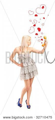 Full length portrait of a female holding a telephone tube, giving kisses and heart shapes around isolated on white background