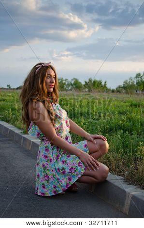 Beautiful girl on the roadside watching the sun