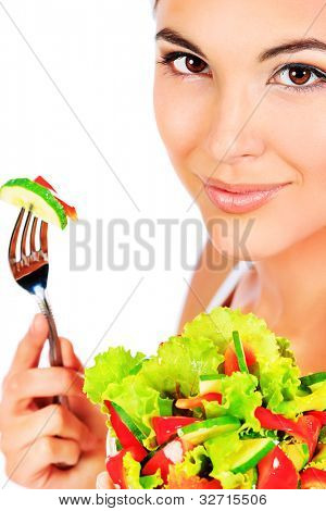 Portrait of a beautiful young woman eating vegetable salad. Isolated over white background.