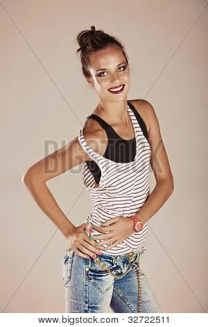 portrait of a trendy young tanned woman wearing striped top and faded jeans with neon bright watch and pink green manicure.