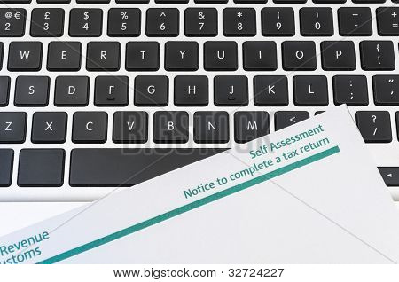 Detail of blank tax return form on top of computer keyboard.