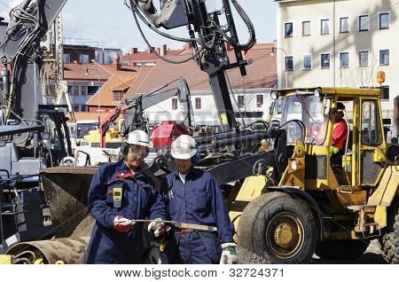 building workers, bulldozers and heavy machinery inside construction industry