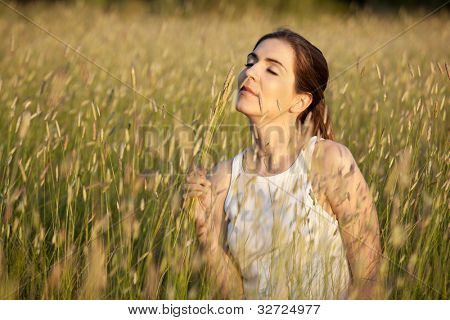 Outdoor portrait of a beautiful woman smelling flowers on a summer day