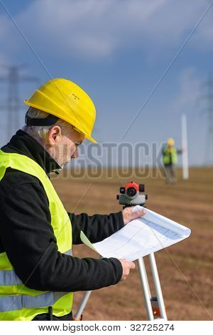 Land surveyors on construction site reading plans measure tacheometer