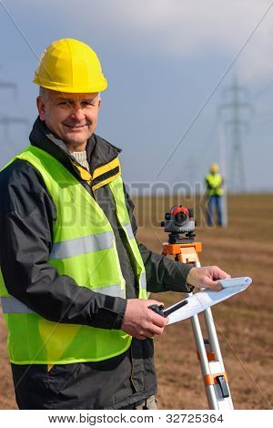 Land surveyors measuring with tacheometer hold construction plans on site