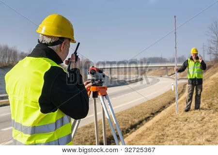 Land surveyors measuring with tacheometer speaking through transmitter highway