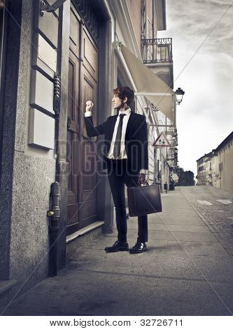 Young businessman knocking at an entrance door