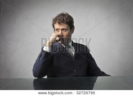 Young businessman sitting at his desk with thoughtful expression