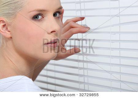 Nosy blond peering through window blinds