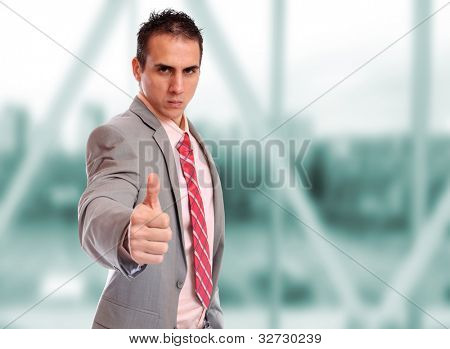 Closeup of a young business man thumb up standing in a light and mordern business hall.