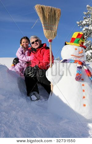 grandfather posing with granddaughter at ski resort