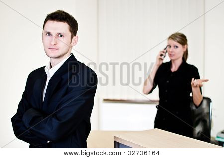 Young Businessman And His Secretary Talking On The Phone In The Office