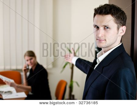 Office Life Scene. Young Businessman Invites To His Office. Place For Own Text On Doors Plate