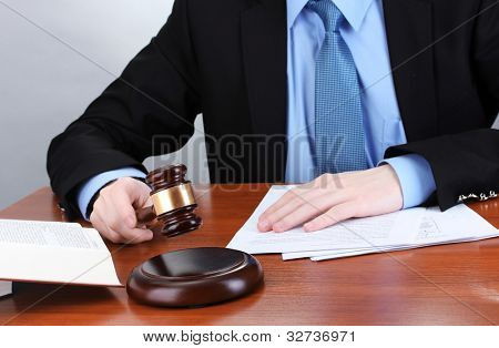 wooden gavel in hand and books on wooden table on gray background
