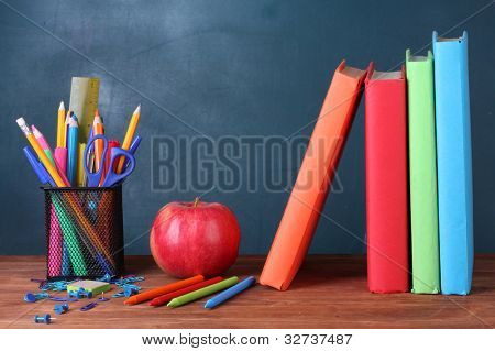 Composition of books, stationery and an apple on the teacher's desk in the background of the blackboard