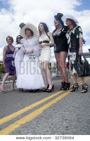 Drag queens pose on the street.