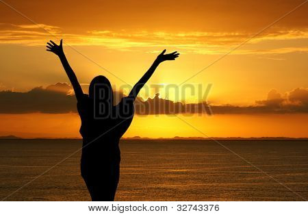 Girl with hands up while standing on the beach