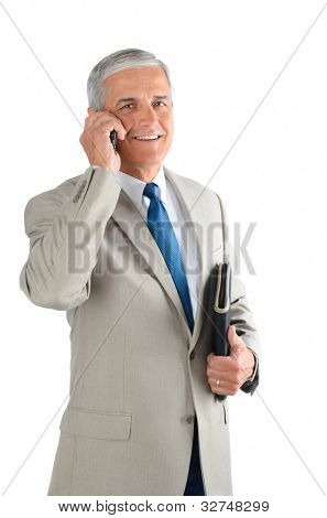 Middle aged businessman talking on his cell phone and carrying a binder. Man is smiling and looking at camera over a white background.