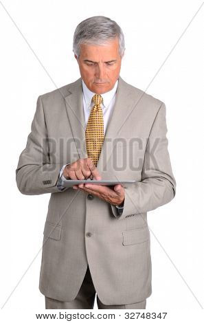Middle aged businessman looking down at the tablet computer in his hands. Vertical format over a white background.