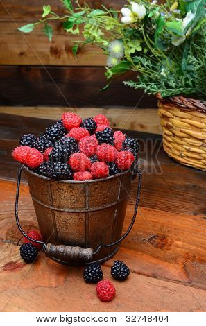 Fresh picked blackberries and raspberries in a galvanized pail on a rustic wooden table. Vertical format