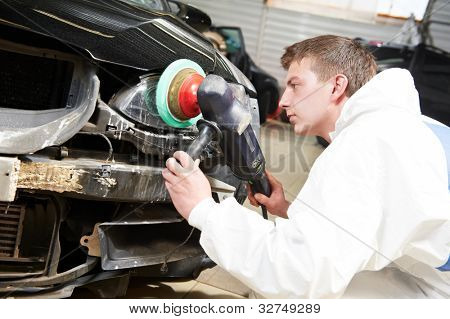 auto mechanic worker polishing car headlight at automobile repair and renew service station shop