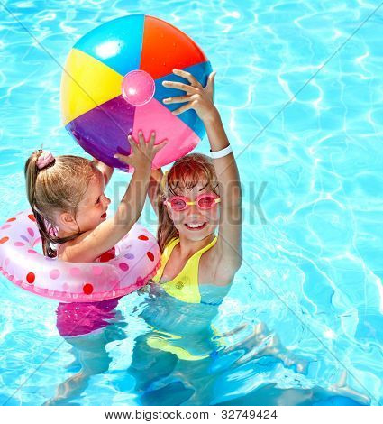 Child playing in swimming pool. Summer outdoor.